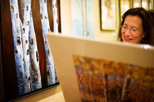 Mary Friedman looks over some of the work on display at the Art Walk showing at Creative Framing. ( Jonathan Castner )