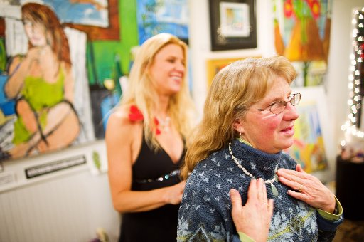 In front, Mary Johnson tries on some of the jewelry of Jeannette Bowles, at rear, during the Art Walk at Bittersweet gallery. ( Jonathan Castner )