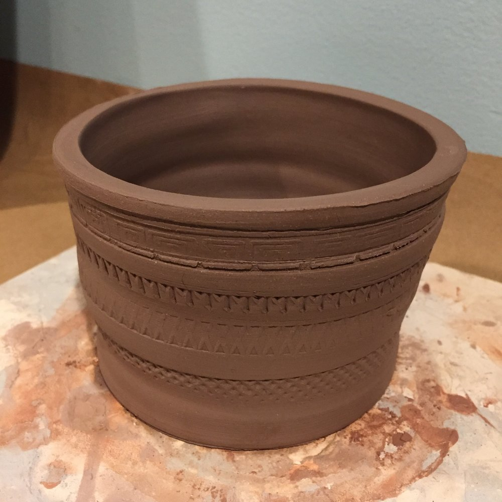 Wheel thrown pot made with stamped designs.