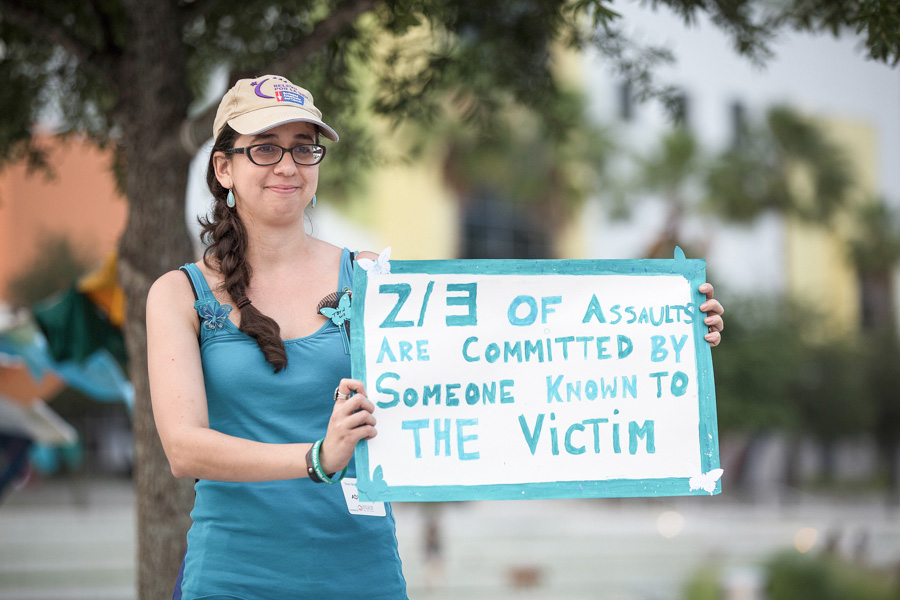 A woman holding a sign about one of many facts of abuse