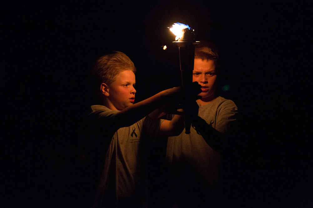 Two boys carrying a torch
