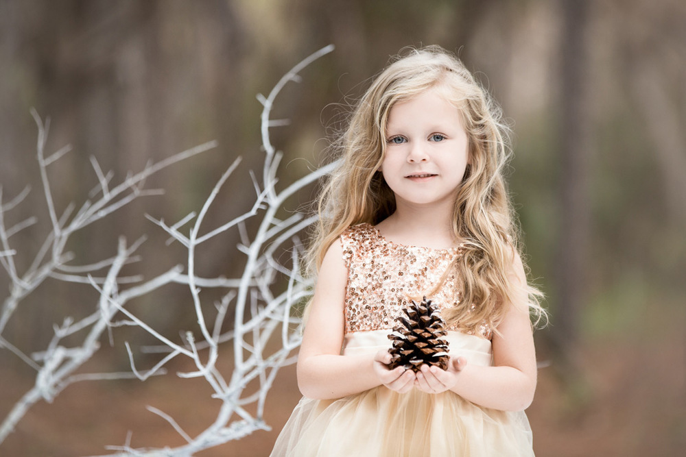 Little girl holding a pinecone