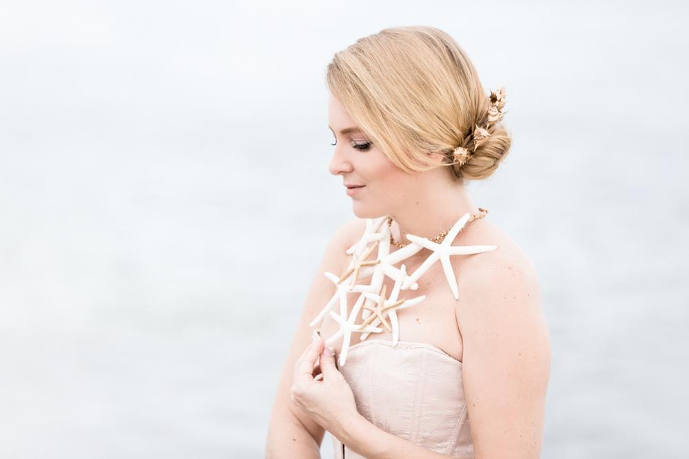 Beautiful woman touching her starfish necklace