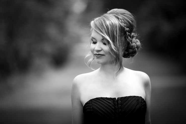 Headshot of a stunning young lady in black couture dress