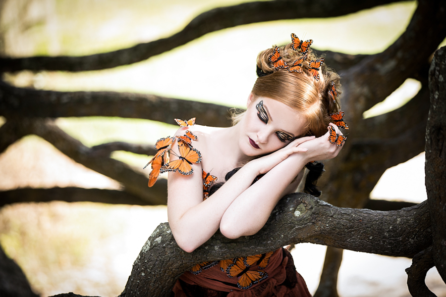 Portrait of a woman dressed as butterfly sleeping in the tree