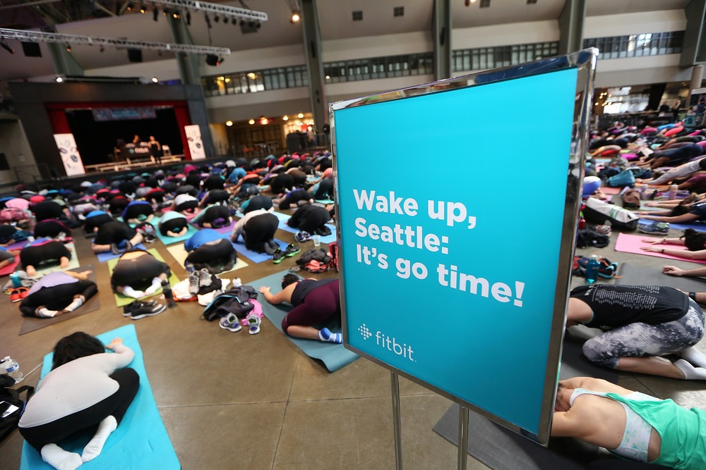 Fitbit Local Ambassadors Kaisa Keranen & Kevin Ng lead participants in a bootcamp and yoga workout as Fitbit Local Seattle launches with a free event at the Seattle Center Armory on March 26, 2016 in Seattle, Washington.