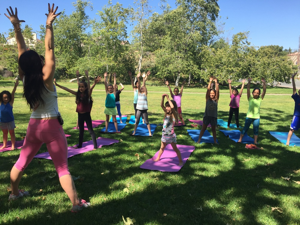 Instructor Lex Ferrier leads young girls through a yoga session at the Ivivva UTC Yogachella event.