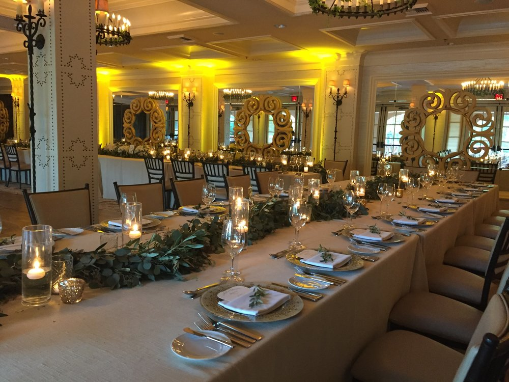 The reception room was lined with long tables that all guests sat, highlighted with candlelight colored uplighting.