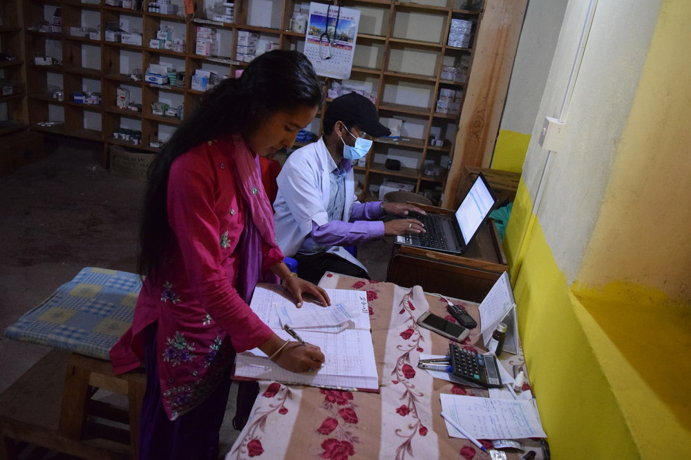 Khalasha assisting lab technician, Tanka, with pharmacy records