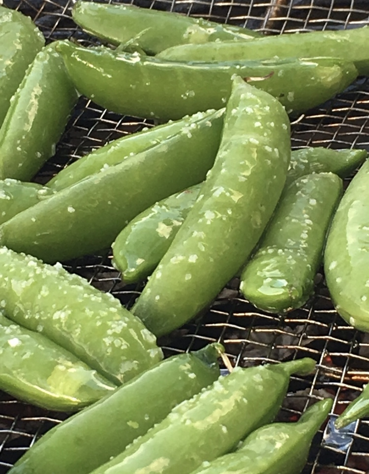 Blistered snap peas sizzling over hot coals.