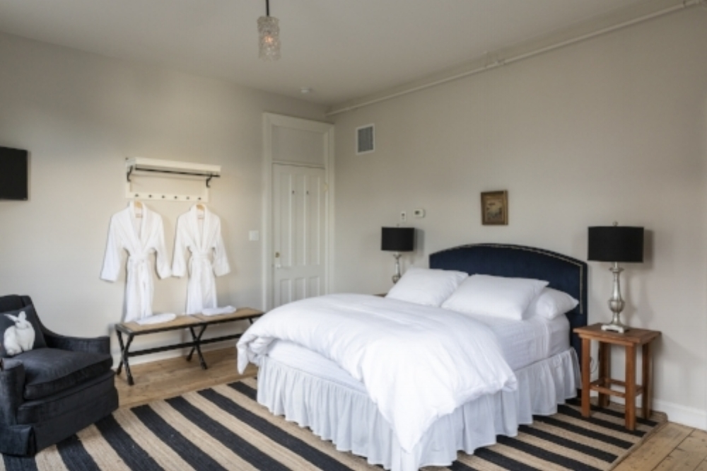Large sunny room with three large river view windows, a queen bed, antique dresser and sitting area with settee and armchair. - 310 sq ft$249.00 per night for up to 2 people