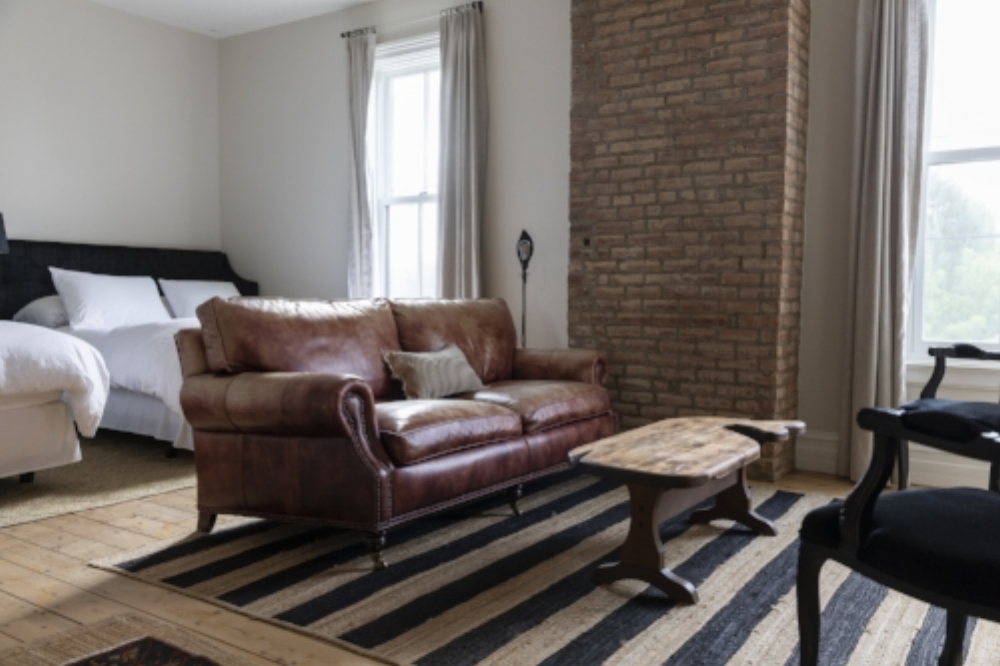 A grand guest room with two queen beds and living area. The two large windows look directly to the Hudson River and the famous Stewart House willow trees and garden. - 390 sq ft$299.00 per night for up to 4 people