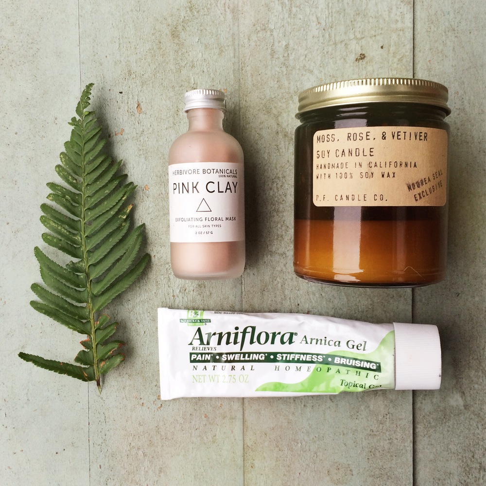 Some of our favorite recovery must-haves: A facial mask to help remove the post-workout sweat and grime, a soothing candle, and Arnica gel for bruises and sore muscles. Not pictured: Epsom Salts, Tiger Balm, supplements like curcumin and fish oil, and a foam roller.
