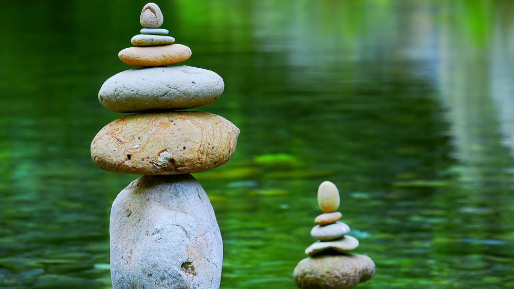videoblocks-close-up-shot-of-rocks-stacked-on-top-of-each-other-and-placed-in-quiet-jungle-lake-meditation-scene-with-stone-piles-by-side-of-water-symbol-of-balance-harmony-and-tranquility-camera-stays-still_s6uptyxyz_.png