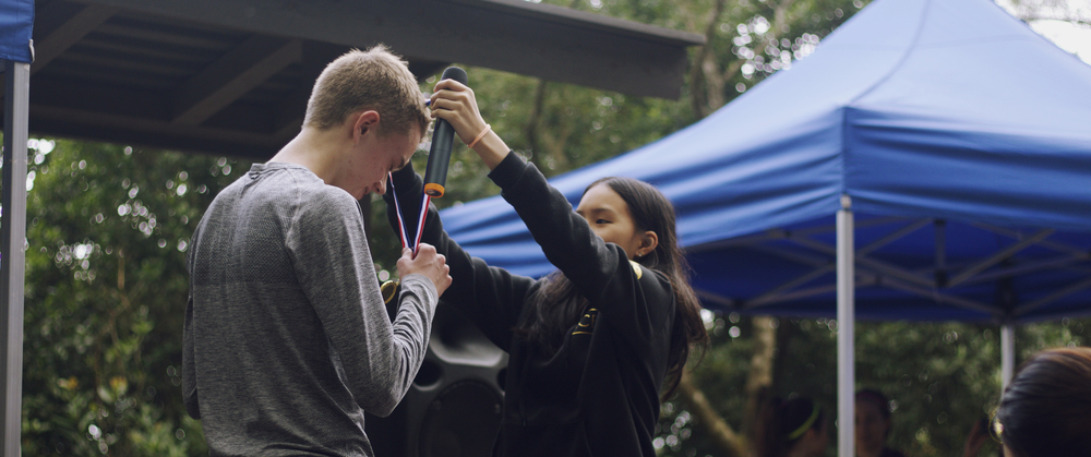 2015 Director Genevieve Hu awards a medal to a runner