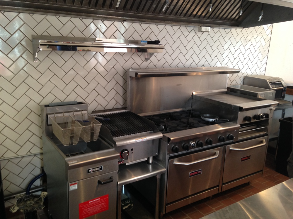 The pristine cookline with the old school check rail (holder). The herringbone tile is a nice touch too.