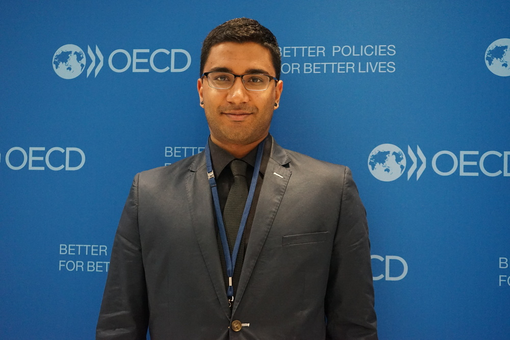 Gautham Krishnaraj (Head Delegate) in front of OECD backdrop.JPG