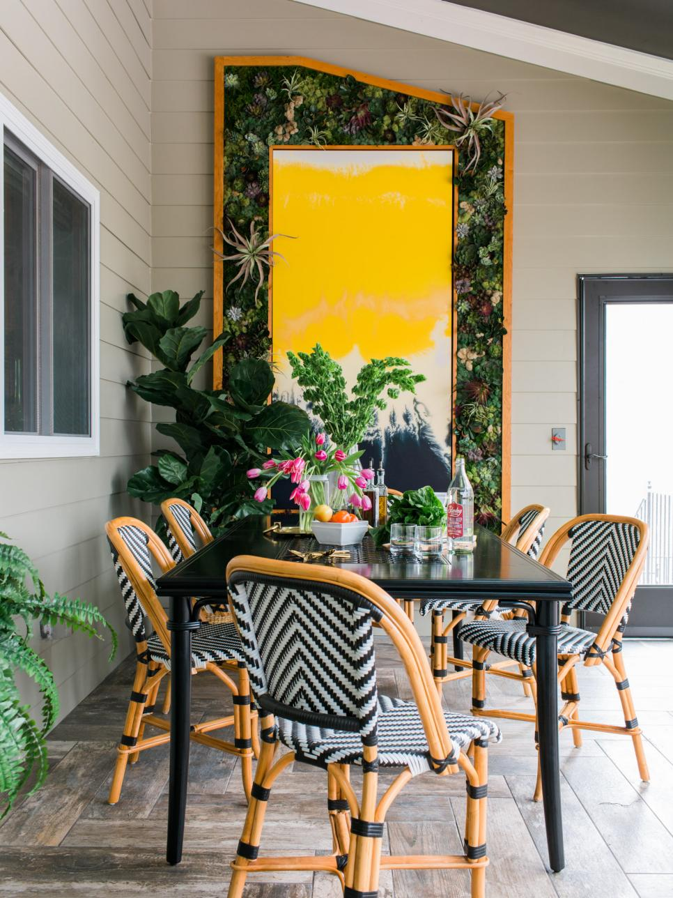 The Living Wall with plants takes up the entire back wall of the screened porch, and frames black, white and yellow abstract art .| Photo by Tomas Espinoza