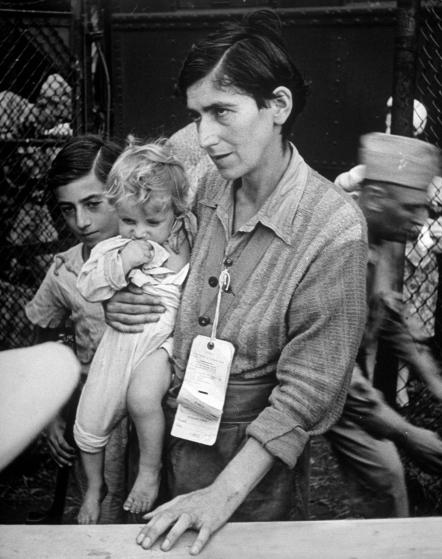 Eva Bass, formerly a night-club singer in paris, entering refugee camp in fort ontario, with her children yolanda and joachim, who she carried on a 60 km trek thru the fighting lines to reach an american transport ship (1944)