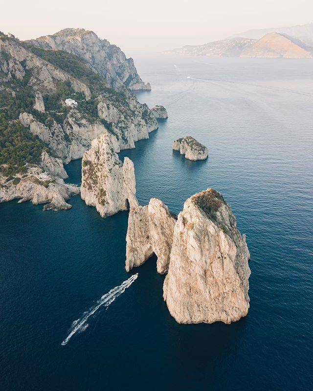 One of my favorite views off the coast of Capri, soaring over Faraglioni 🚁: @larswyder