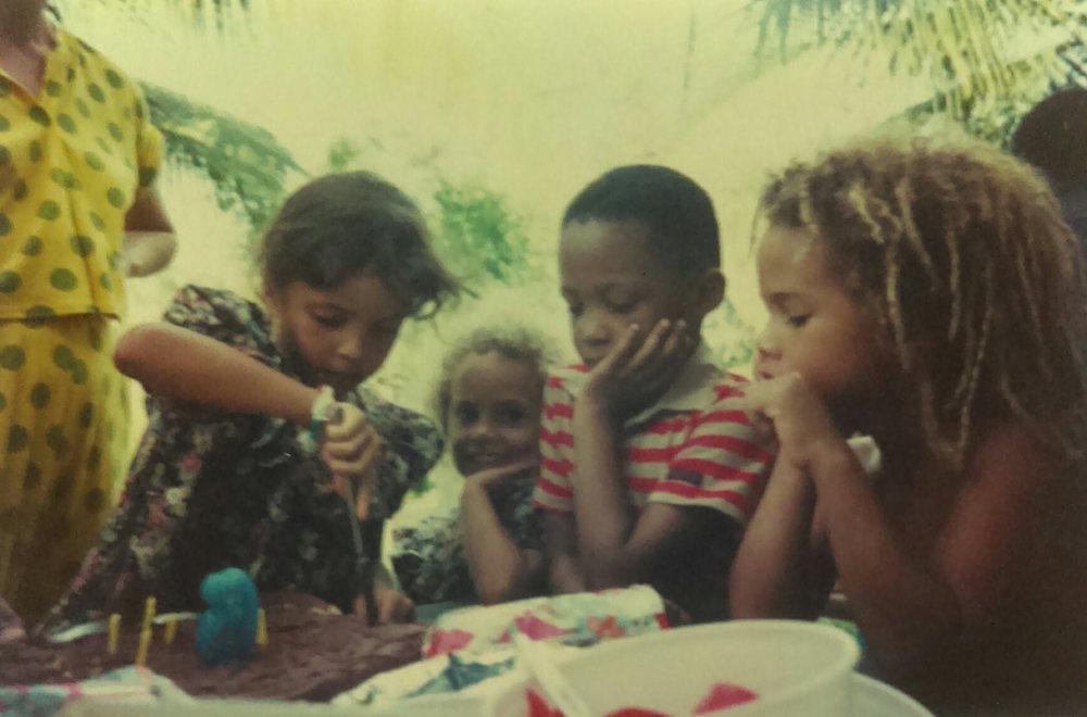 """MD_001_018    Cumpleanos de Jackie    Playa Chiquita    2/14/1993    Fiesta de cumpleanos de Jackie Bryan en el patio de """"Church House"""" propiedad de los Bennett. Monica Donley (parada), Jackie Bryan, Simone Bryan, nino desconocido, Daniel Brown"""