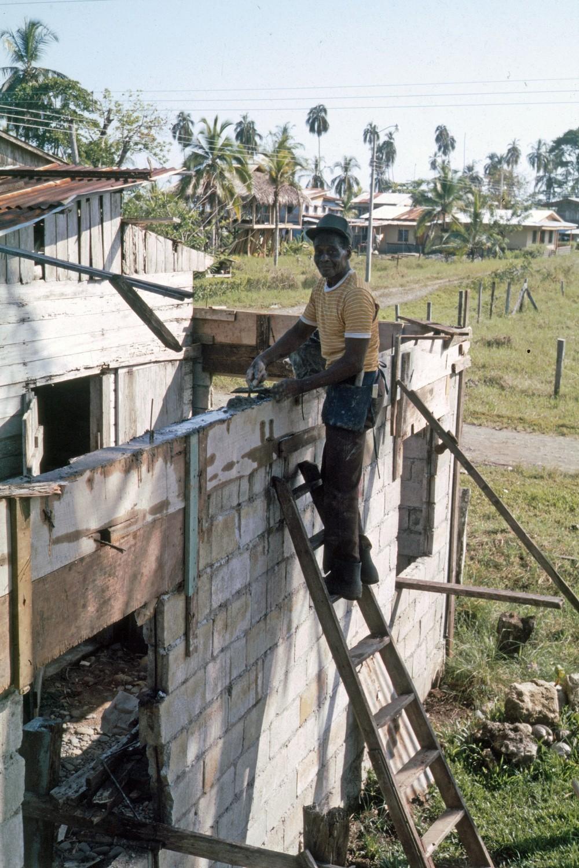 Mr. Patterson Construyendo    Puerto Viejo    1986    Mr. Patterson construyendo con cemento nueva casa alrededor de casa vieja de madera en el fondo casa de Aldo en consrucción con techo de hojas    CZ_001_010