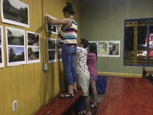 Students hang photographs from the South Caribe Roots Archive for a local gallery at the Casa de la Cultura
