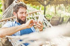 caucasian-man-using-app-his-mobile-phone-swinging-hammock-61748337.jpg