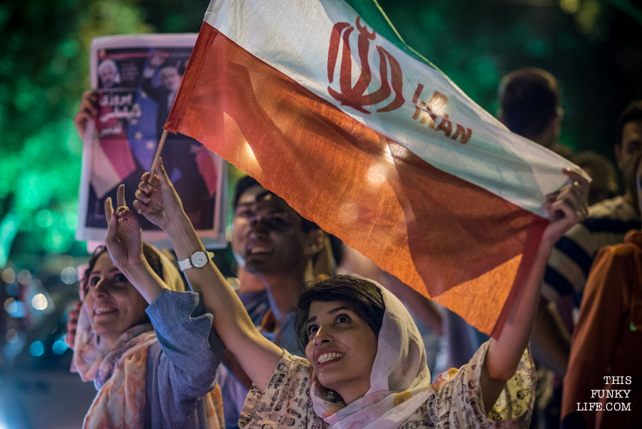 "Waving flags and holding up a newspaper which said ""Victory of Diplomacy"""