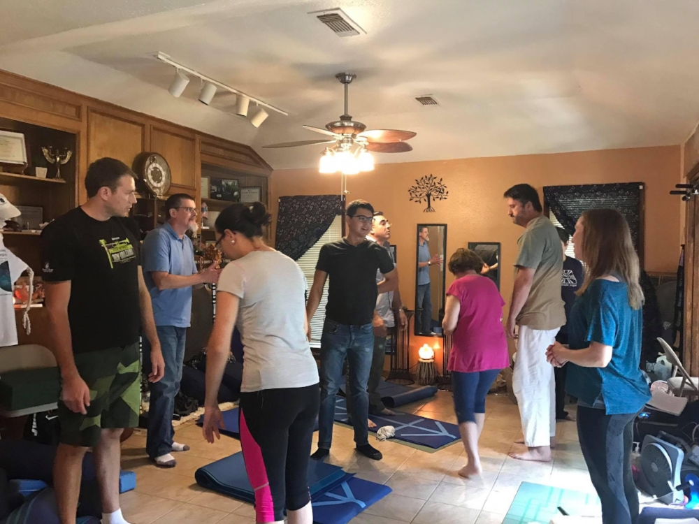 The author (right) leading a postural alignment assessment and answering questions for a group class at  Peaceful Winds Yoga Studio  . ( (Credit: Bonnie Palmer Reed.)