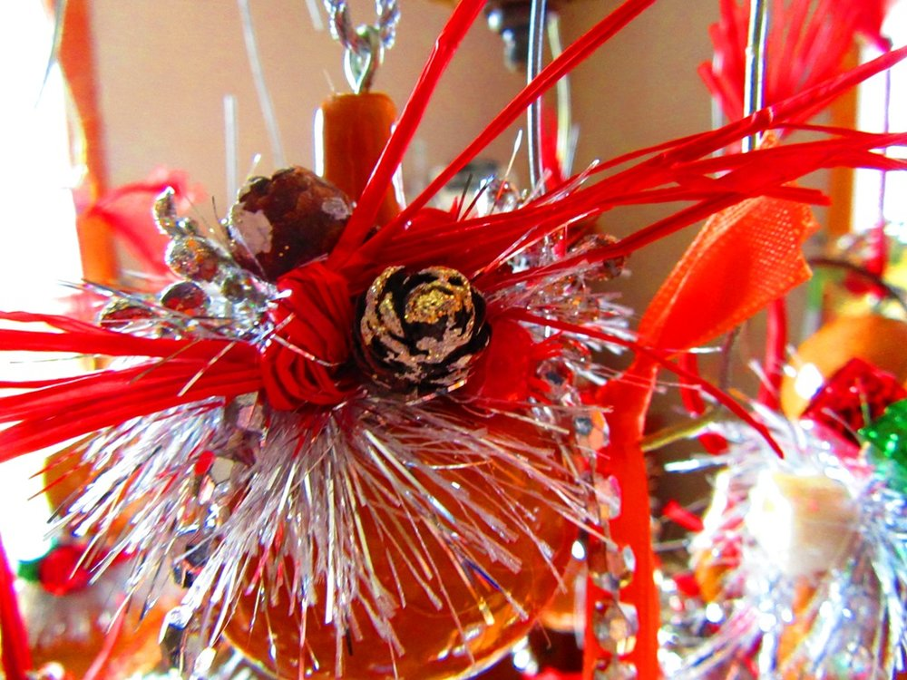 mini-cones, berries, red raffia, silver feathery garland, sparkling beads, mini ceramic presents