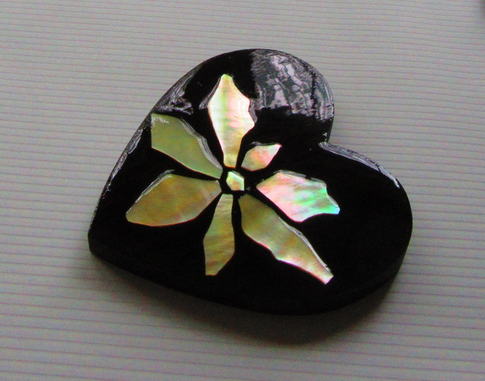 Ebony wood heart with Golden Mother-of-Pearl poinsettia inlay (the poly finish reflects different images and colors)