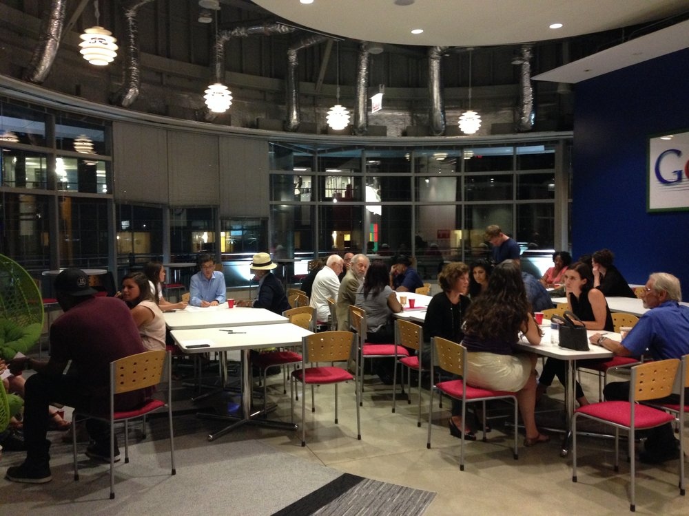 Attendees sit around tables at Google in Chicago working on social impact/marketing case studies.