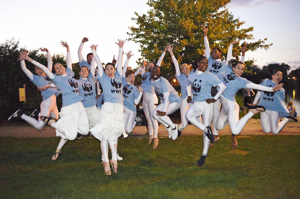 Fantasmagorie dancers jump in the air for an active pose, wearing WWF Panda t-shirts!