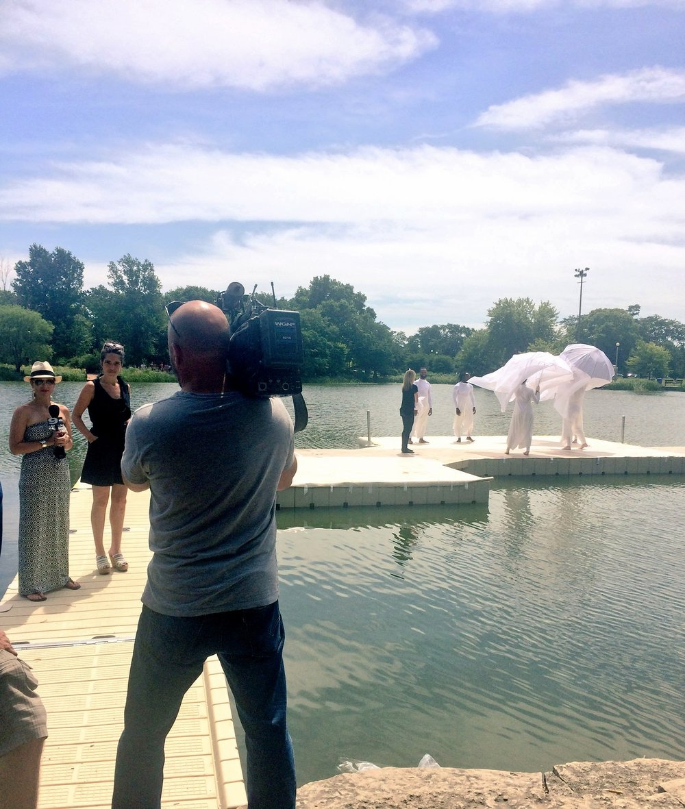 Josie Davis interviews with WGN crews on the docks at Humboldt Park Lagoon, with dancers in the background.