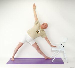 Take a wide stance with your feet (3-4 feet) and turn the foot nearest the chair, toward the chair. Make sure your feet are stable and in full contact with the floor. Tighten your core and raise your arms parallel to the floor. Tilt your torso forward and bring your front hand to the seat of the chair for support while rotating your top shoulder open. 9.      DOWN DOG