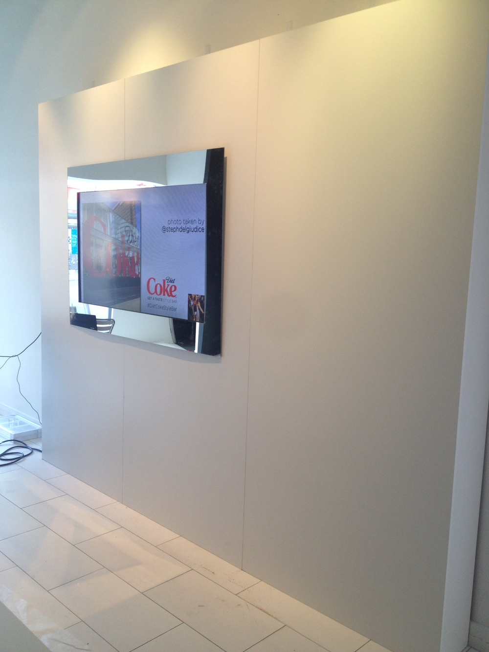 Custom free-standing divider wall with mirrored TV frame
