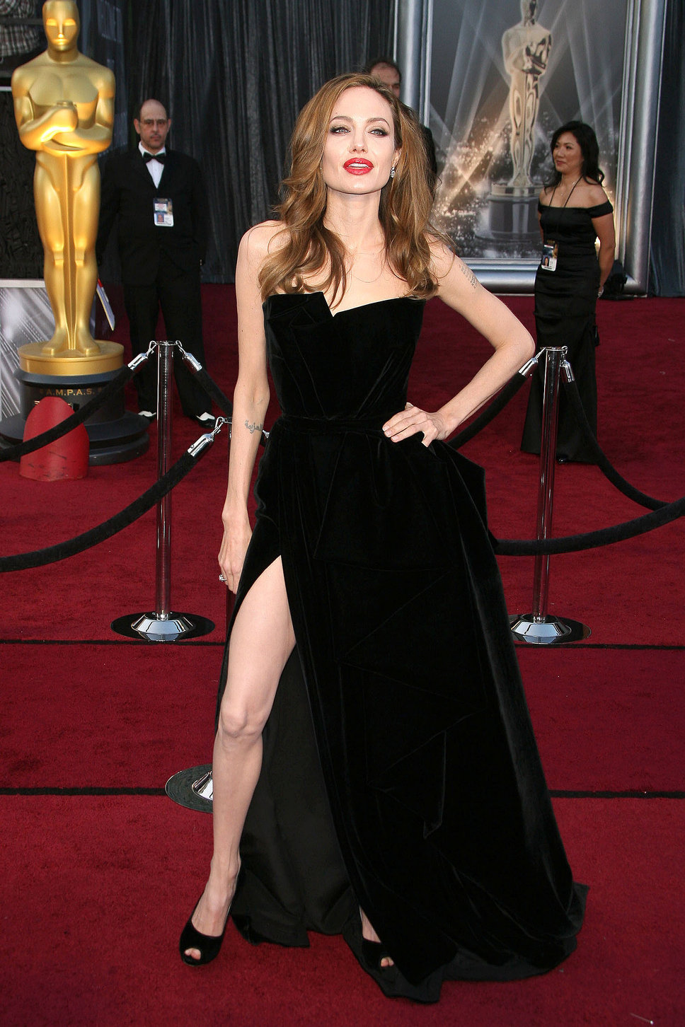 Angelina Jolie, in 2013, wearing a black dress by Versace, doing her (in)famous leg pose!