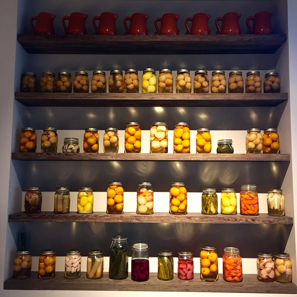 A wall of  various jars homemade pickles.
