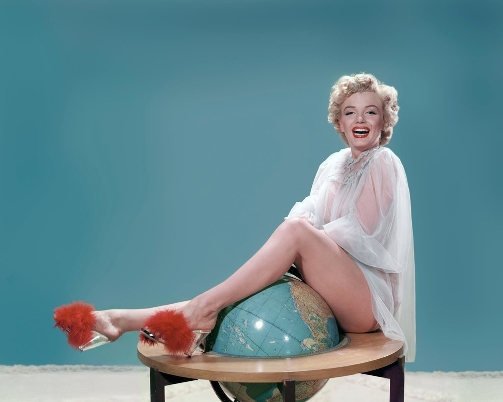 Marilyn Monroe, literally on top of the world, wearing nothing much besides her furry mules!