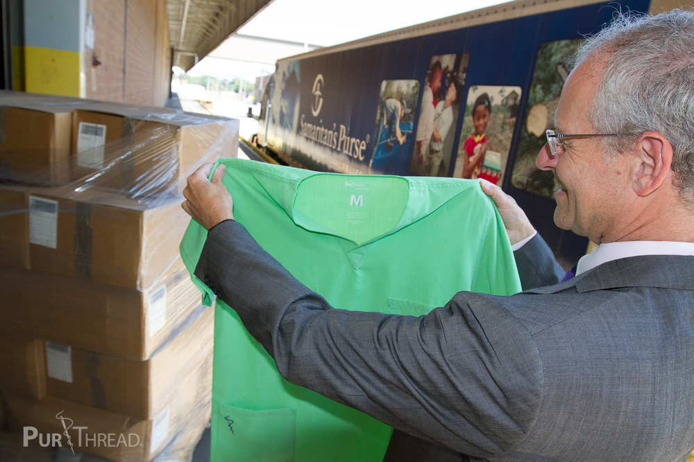 PurThread Medical Director, Russ Greenfield, MD, oversees the handoff of scrubs and privacy curtains to Samaritan's Purse.