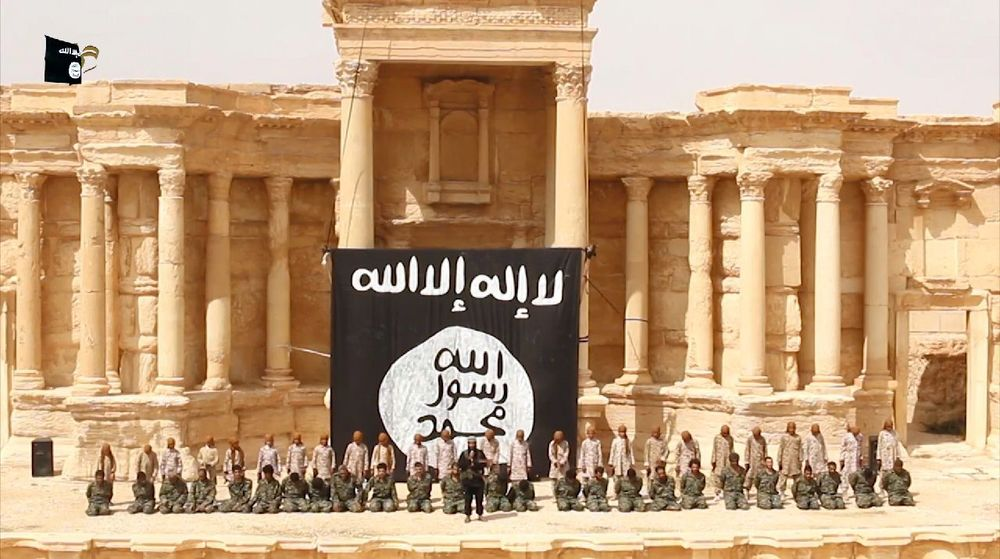 25 Syrian government soldiers kneel in the ancient amphitheatre in the city of Palmyra ahead of being executed by children. Photo by Welayat Homs.