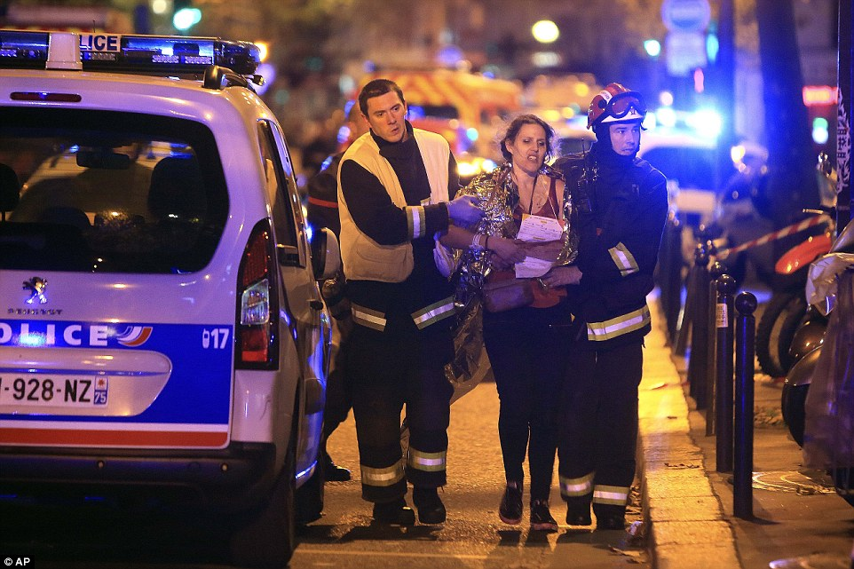 Rescue workers help a woman after a shooting, outside the Bataclan theatre in Paris. Photo by AP Images
