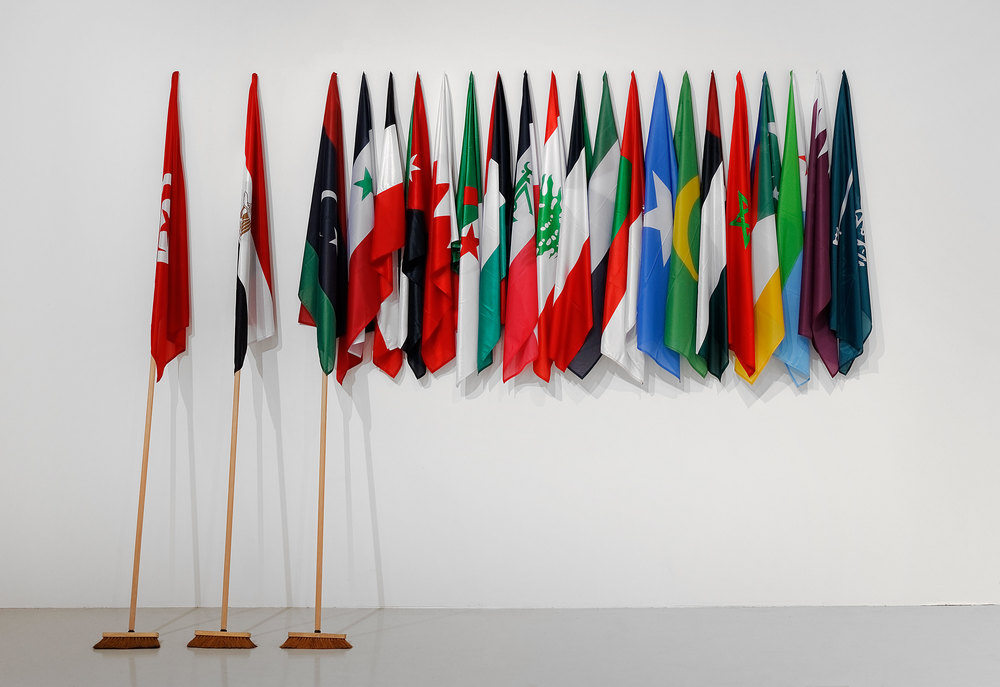 The Lost Springs, October 2011, 3 brooms of 3 meters, 22 flags or arabian countries, 300 x 405 x 40 cm. Courtesy of the artist and Goodman Gallery, Johannesburg-Cape Town. Exhibition view from Le Monde Selon…, FRAC Franche Comté-Besançon, 2015. Photo credit : Blaise Adilon
