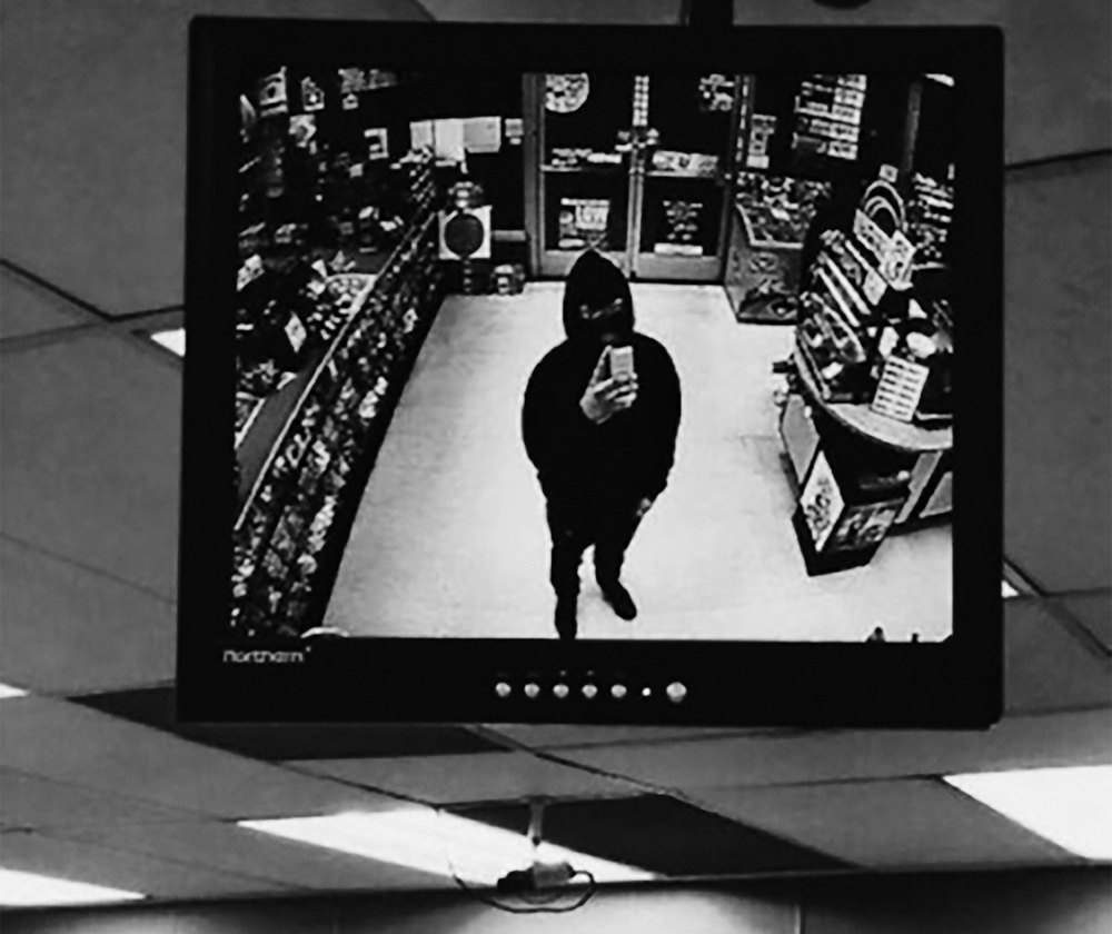 An untitled still from a CCTV footage of a shop robbery.