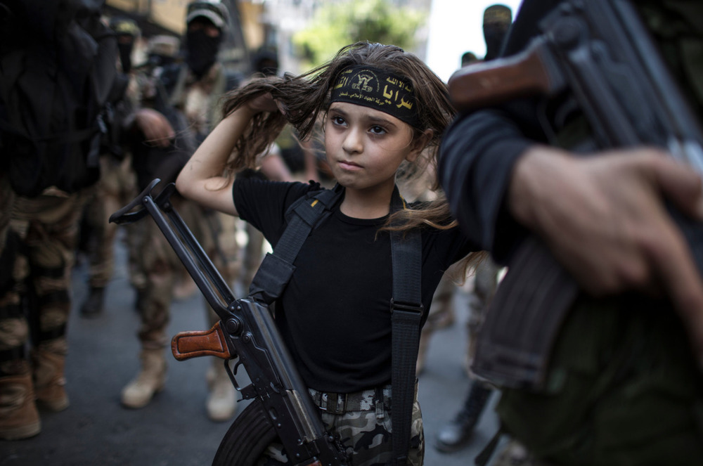 A Palestinian girl with a Kalashnikov rifle, amid Islamic Jihad militants in Gaza City 2004 by Wissam Nassar for The New York Times.