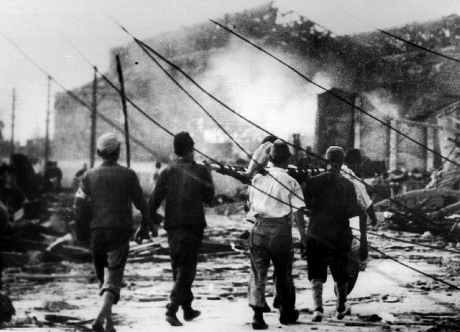 Japanese air raid workers carry a victim of the atomic bomb in Hiroshima away from smoking ruins on 6th August 1945. Photo source: Reuters.