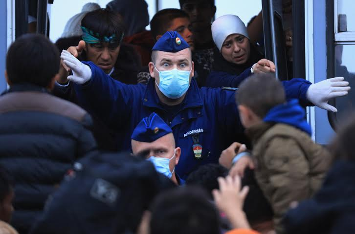 A Hungarian police officer tries to prevent refugees from boarding a bus at the refugee camp in Röszke. Photo by Christopher Furlong/Getty Images.
