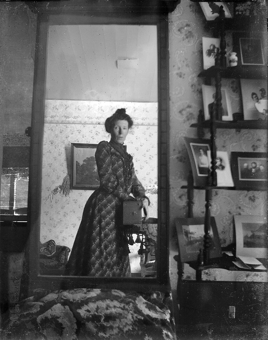 Photographer Margrét Möller taking a self-portrait using a mirror and a box camera, circa 1900.