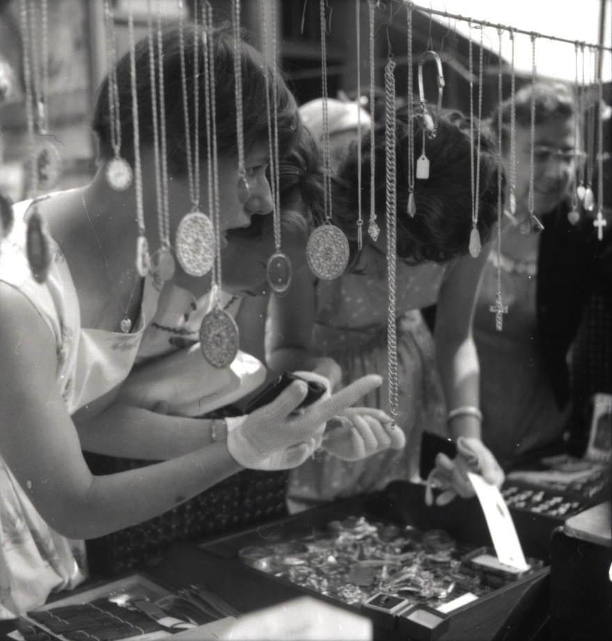 A group of women examine the contents of a stall selling jewellery on  Portobello Road Market, 1955. Photo source: T he RBKC Library.